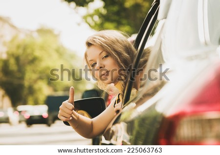 Beautiful caucasian young woman in car showing the thumb up - stock photo