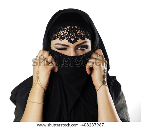 Beautiful caucasian young woman with black veil on face, one eye closed, fancy arabian costume - stock photo