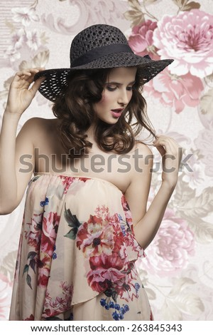 Beautiful, charming, etheric woman with brown, curly medium hair, wearing summer hat and delicate dress with floral pattern. - stock photo
