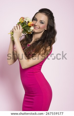 Beautiful, charming, romantic woman with brown, long, curly hair. She is wearing pink, sexy dress and necklace and holding bouquet of spring flowers. - stock photo