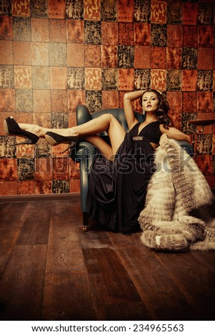 Beautiful charming woman in elegant evening dress and fur coat in a classic interior. Fashion, glamour. - stock photo