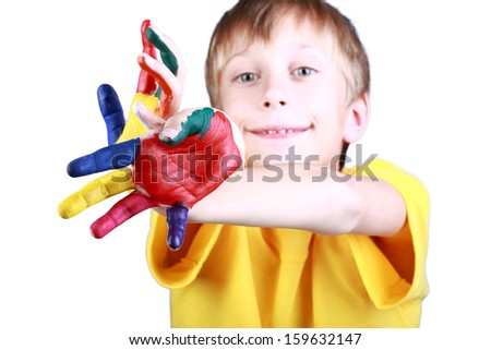 Beautiful cheerful blond boy in a yellow t-shirt showing multicolored painted hands (selective focus) - stock photo