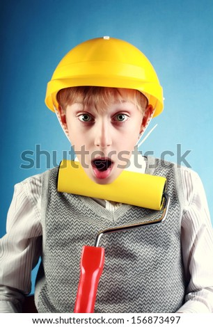 Beautiful cheerful blond boy wearing a yellow hard hat holding a painting roller looking surprised on blue background - stock photo