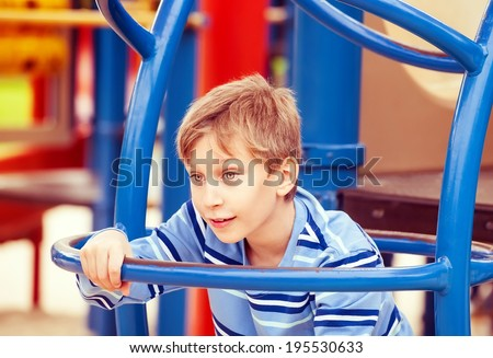 Beautiful cheerful child playing on a colorful playground climbing looking excited  - stock photo