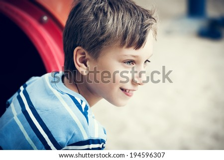 Beautiful cheerful child playing on a playground in summer looking excited  - stock photo