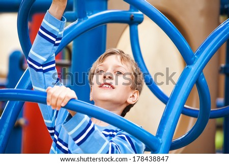 Beautiful cheerful child playing on a playground smiling - stock photo