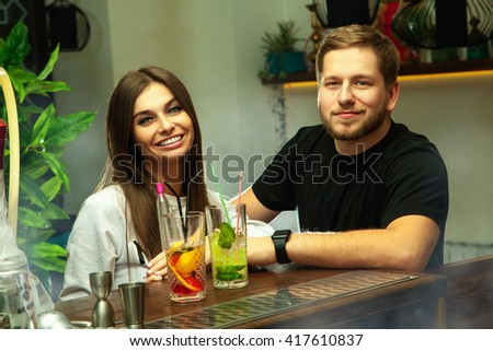 beautiful cheerful couple at the bar drinks cocktails and having fun - stock photo