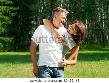 Beautiful cheerful couple in summer park - stock photo