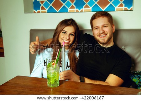 Beautiful cheerful couple in the bar smoking shisha and drinks cocktail smiling on camera - stock photo