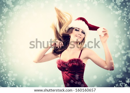 Beautiful cheerful fashion christmas girl dancing in party in Santa's hat in snow, toned - stock photo