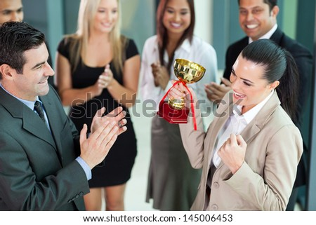 beautiful cheerful female corporate worker receiving a trophy from company CEO - stock photo