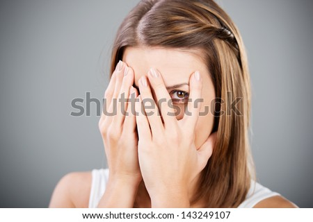 Beautiful cheerful female covering her face using hands - stock photo
