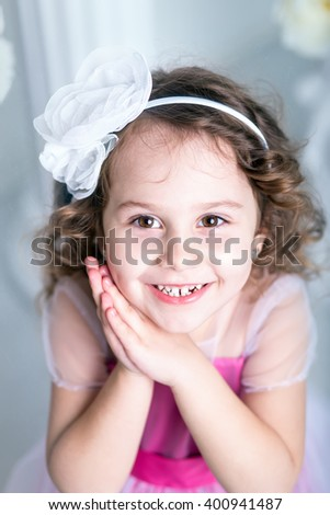 Beautiful cheerful girl four years old with clasped hands under her cheek - stock photo