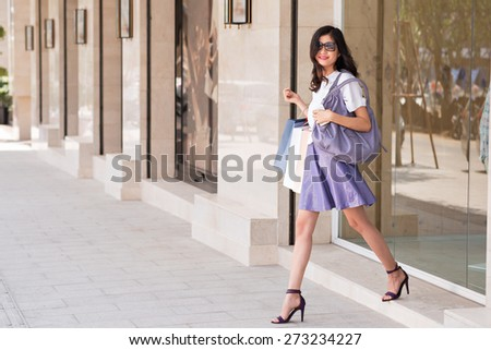 Beautiful cheerful girl with shopping bags walking out of the store - stock photo