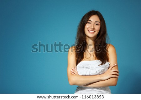 beautiful cheerful teen girl in white top over blue background - stock photo