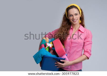 Beautiful cheerful woman holding different cleaning stuff. Isolated - stock photo