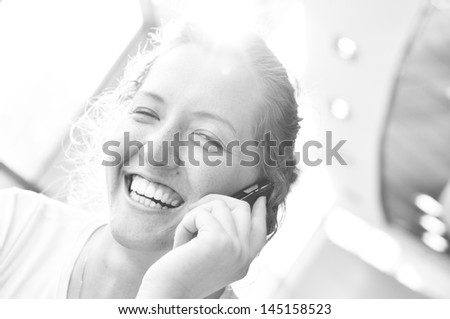 beautiful cheerful woman is talking phone in sunny cafe - stock photo