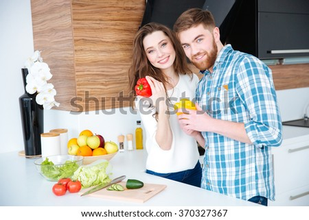 Beautiful cheerful young couple cooking healthy food on the kitchen together - stock photo