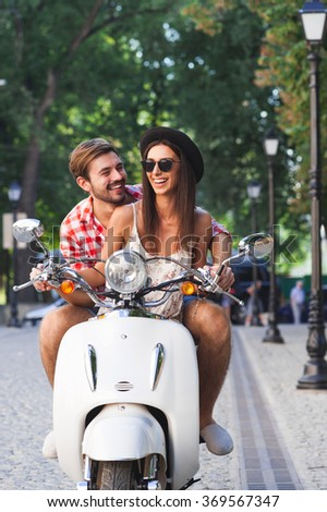 Beautiful cheerful young couple learning to ride a vintage white scooter together. Young man teaching his hipster girlfriend to drive motorbike - stock photo