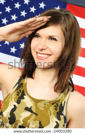 beautiful cheerful young woman dressed in camouflage salutes opposite an American flag - stock photo