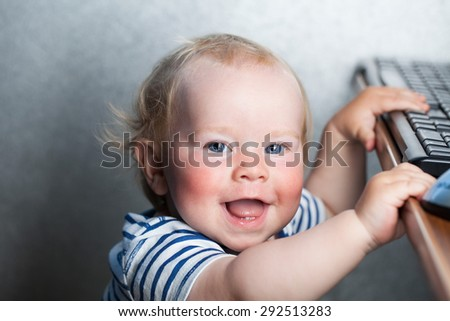 beautiful child boy blond mischievous smile hands on a computer keyboard - stock photo