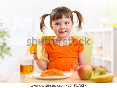 Beautiful child girl eating healthy food fruits at home - stock photo
