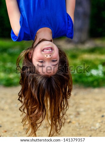beautiful child hanging upside, laughing, with greenery in the background - stock photo