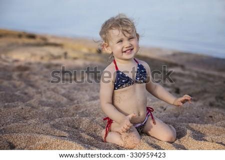 Beautiful child on the beach, playing castley. Ocean, swim, bikini, summer, beach, resort - stock photo
