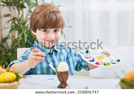 Beautiful child painting eggs wth brush and holding color palette - stock photo
