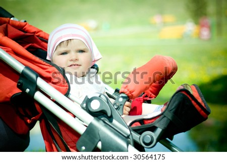 Beautiful child sitting in baby carriage - stock photo