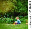 Beautiful child sitting in summer park. Green nature background - stock photo