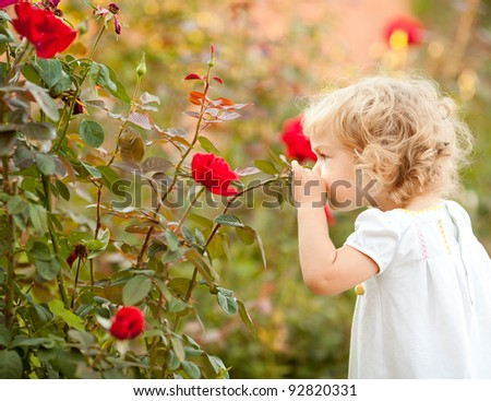 Beautiful child smelling rose against spring flowery background - stock photo