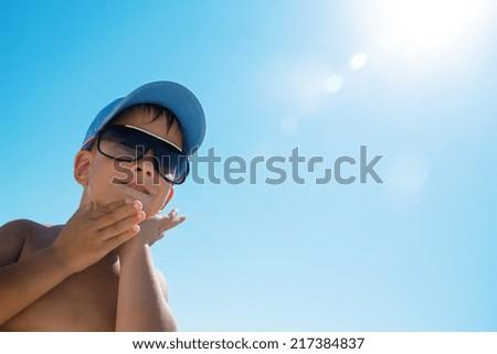 Beautiful child wearing blue cap on beach - stock photo