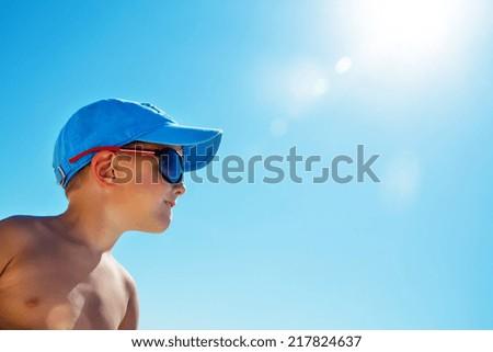 Beautiful child wearing colorful sunglasses looking on sun - stock photo