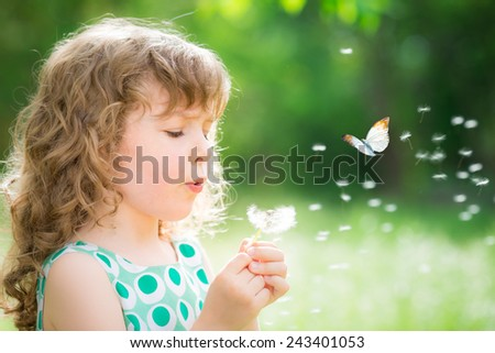 Beautiful child with dandelion flower in spring park. Happy kid having fun outdoors - stock photo