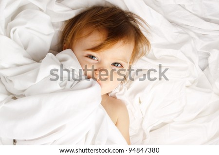 Beautiful child wrapped in white sheets - stock photo