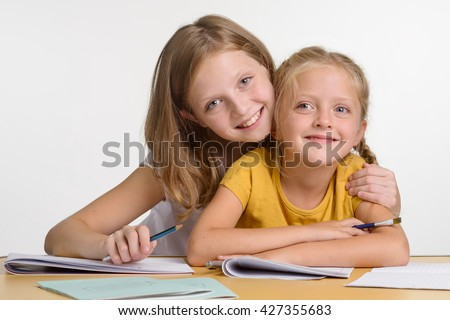 Beautiful children look right in the camera with big blue eyes. The elder sister embraces her young sibling. Lovely family portrait. - stock photo
