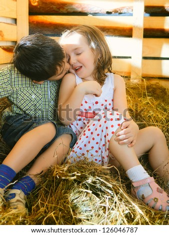 beautiful children on hayloft at sunny day - stock photo