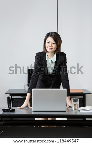 Beautiful Chinese Business Woman leaning on her desk. - stock photo