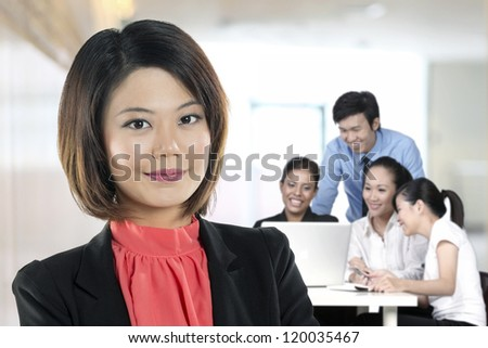 Beautiful Chinese Business woman with colleagues working behind. - stock photo