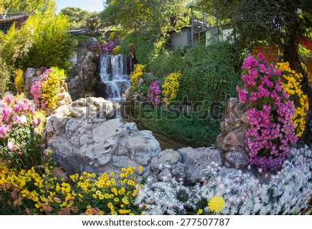 Beautiful Chinese garden with a pond and flags - stock photo