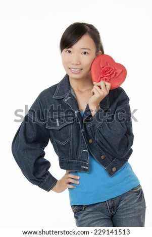 Beautiful Chinese woman holding a red heart and flirting with someone isolated on a white background - stock photo