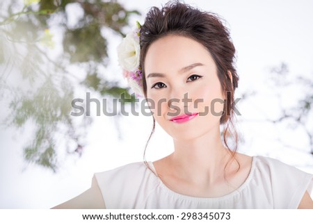 Beautiful Chinese woman with flowers in her head smiling and looking at the camera - stock photo