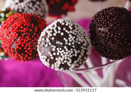 Beautiful chocolate cake pops with colorful candy sprinkles macro in the glass. horizontal - stock photo
