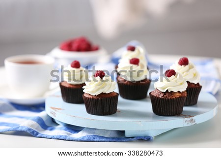 Beautiful chocolate cupcakes with cream and raspberry on table - stock photo