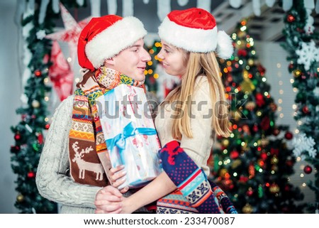 Beautiful Christmas. A loving couple looking at each other while holding Christmas presents. Young couple in love man and pretty girl wearing sweater and scarf at home - stock photo