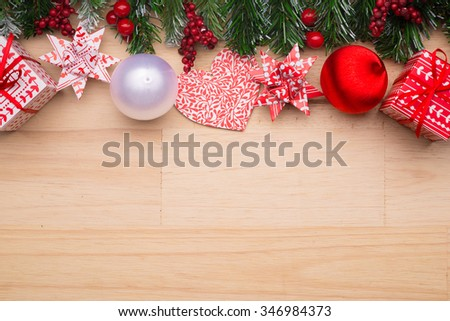 Beautiful christmas background: Collection of Red Christmas objects isolated on fir branches on wooden background with copyspace. View from above - stock photo