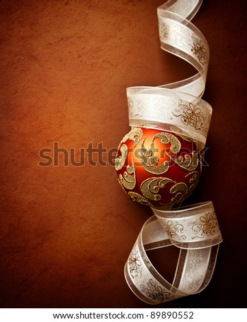 Beautiful christmas ball and gift ribbon on rustic background - stock photo