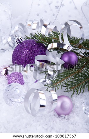 beautiful christmas decoration in purple and silver on white snow sparkle - stock photo