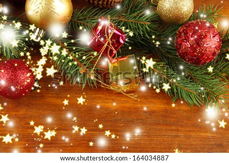 Beautiful Christmas decorations on fir tree on wooden background - stock photo